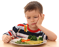 boy thinking about eating his vegetables